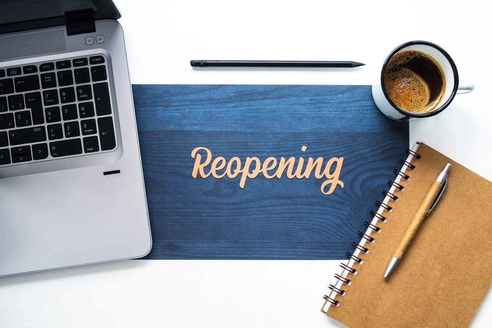 laptop with spiral notebook cup of coffee and sign displaying reoopening in gold letters